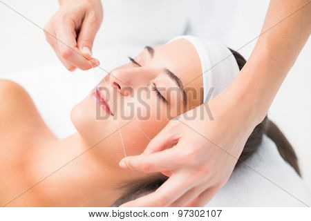 Close up of a hands threading beautiful womans upper lip