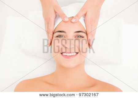 High angle view of an attractive young woman receiving facial massage at spa center