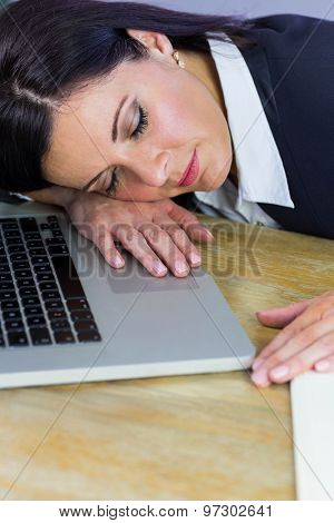 Businesswoman taking a nap on her desk in her office