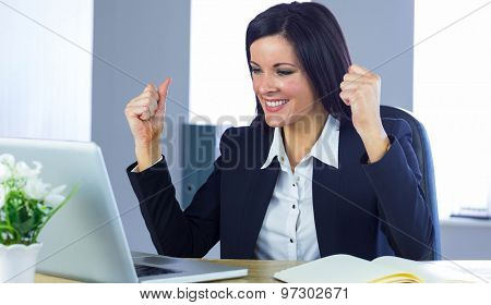 Businesswoman cheering at her desk in her office