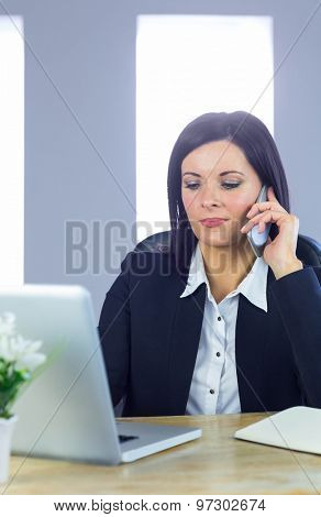Businesswoman on a call at her desk in her office