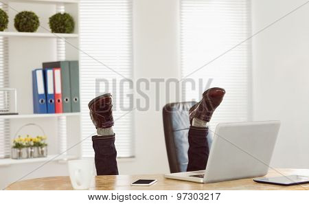 Businessman upside down at his desk in his office