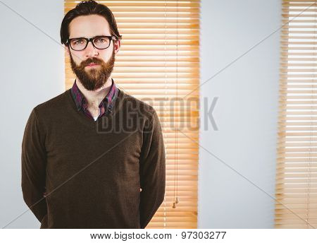 Hipster businessman looking at camera in his office