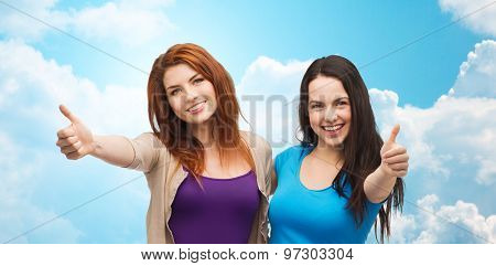 friendship and happy people concept - two smiling girls or young women showing thumbs up over blue sky with clouds background