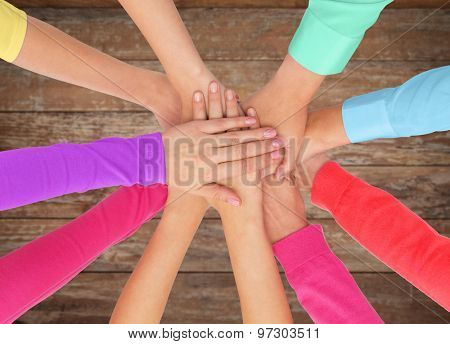 people, gesture, gay pride and homosexual concept - close up of women hands in rainbow clothes on top of each other over wooden background