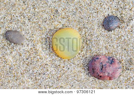 Four Small Stones On A Sand