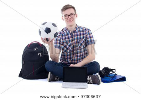 Happy Teenage Boy Sitting With Laptop, Backpack And Soccer Ball Isolated On White