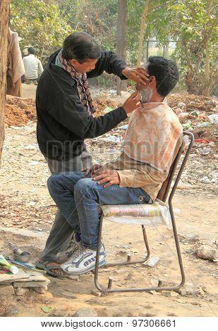 unidentified barber shaving man on the street