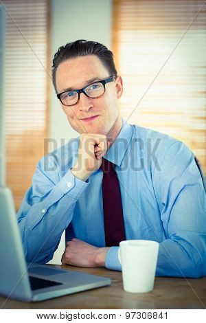 Happy businessman sitting at his desk in his office