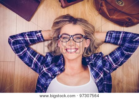 Close up view of gorgeous smiling blonde hipster lying on wooden floor