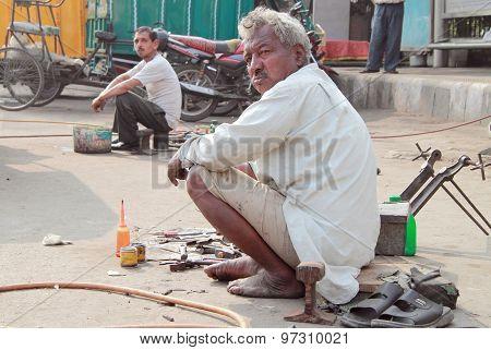 repairmen on the street in Delhi, India