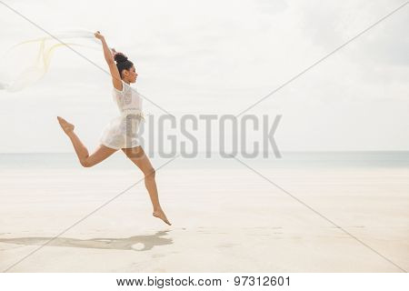 Stylish woman leaping with scarf at the beach
