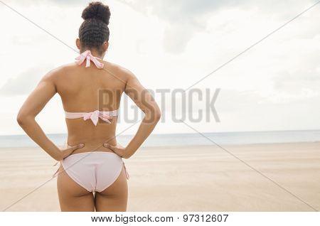 Fit woman in bikini looking to sea at the beach
