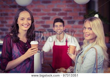 Portrait of a waiter and two customers at the coffee shop