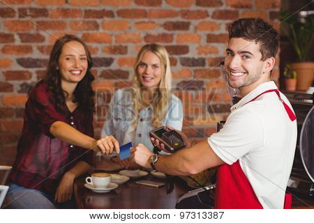 Portrait of friends handing a credit card at the coffee shop