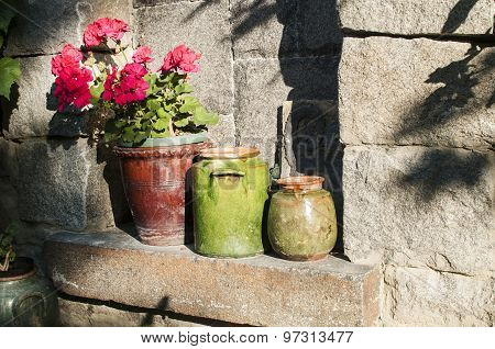 Clay pots with flowers on stonewall