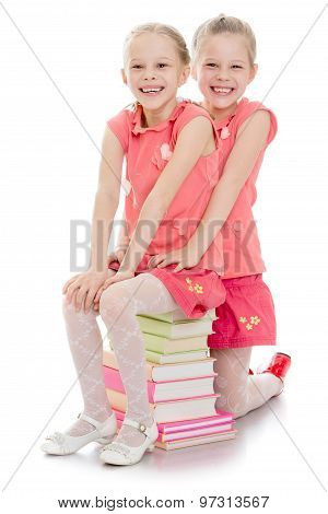 Two sisters sitting on the books