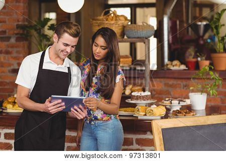 Smiling waiter showing pretty customer tablet at coffee shop