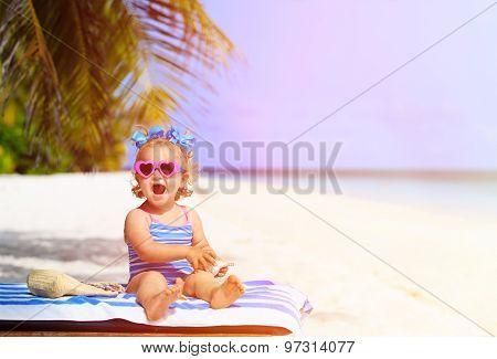 cute little girl with seashells on summer beach