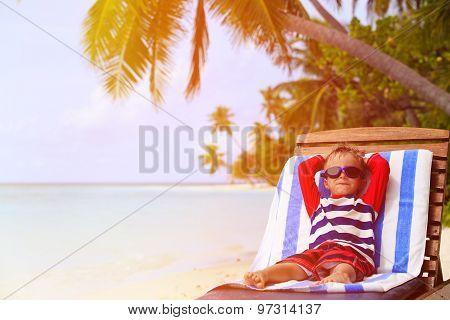 little boy relaxed on summer beach