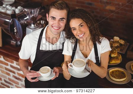 Portrait of smiling waiter and waitress holding cup of coffee at coffee shop