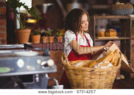 Smiling waitress putting bread in a paper bag at the coffee shop