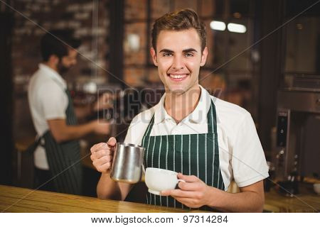 Portrait of a barista pouring milk in a cup at the coffee shop