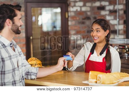 Customer handing a credit card to the waitress at the coffee shop