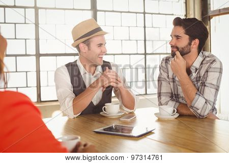 Smiling friends talking and having coffee together at coffee shop