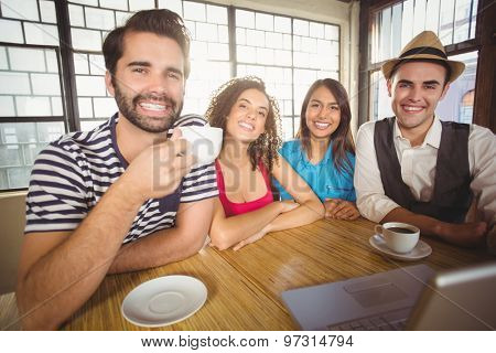 Portrait of smiling friends enjoying coffee together at coffee shop