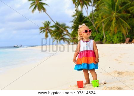 cute toddler girl playing on tropical beach