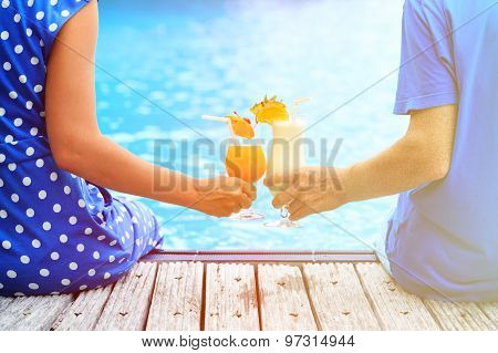 couple drinking cocktails near pool or beach