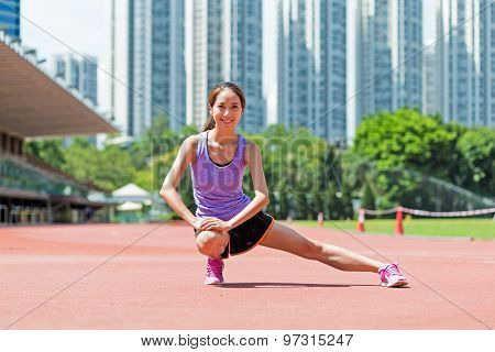 Woman doing stretches exercise in sport arena