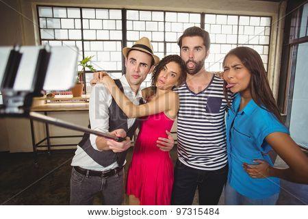 Grimacing friends taking selfies with selfiestick at coffee shop