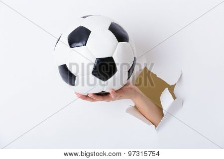 Hand holding soccer ball through the paper hole