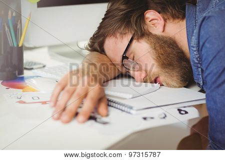 Hipster businessman sleeping at his desk in his office