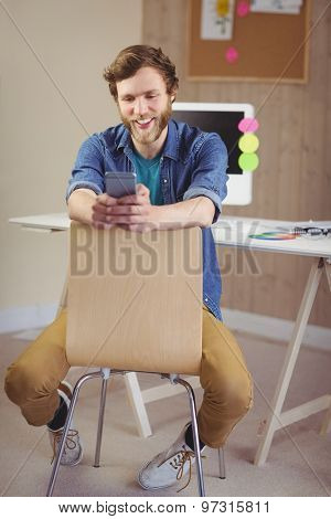 Hipster businessman sending a text in his office