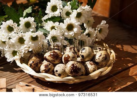 Quail Eggs In A Basket And Flowers.