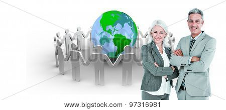 Smiling businesswoman and man with arms crossed against human figures surround earth