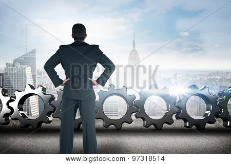 Businessman standing back to the camera with hands on hip against cityscape