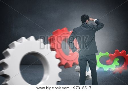 Businessman standing hand on hip against black wall