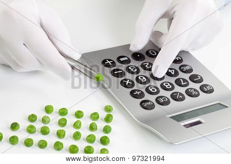 Man Holding Pea In Tweezer While Using Calculator