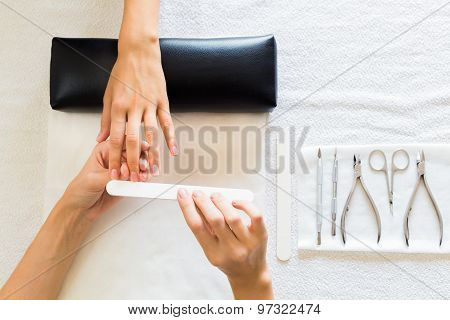Beautician performing manicure on a lady