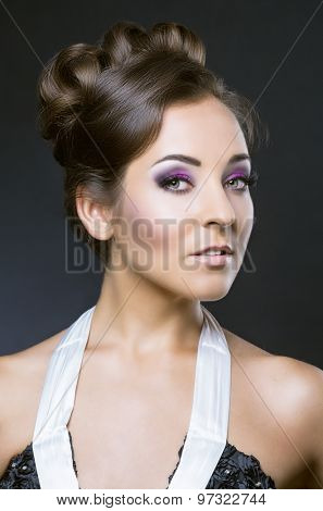 young brunette woman with beautiful makeup and hair, against dark studio backround