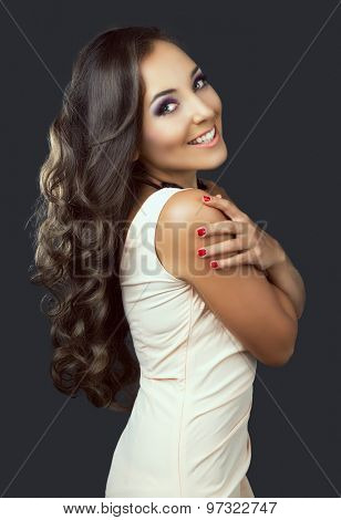 beautiful young brunette woman with long curly hair, against dark grey studio background