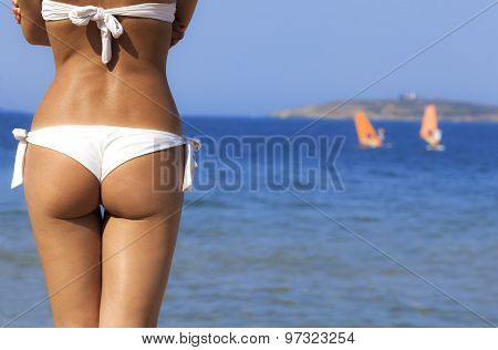 Beautiful girl buttocks on a blue sea background