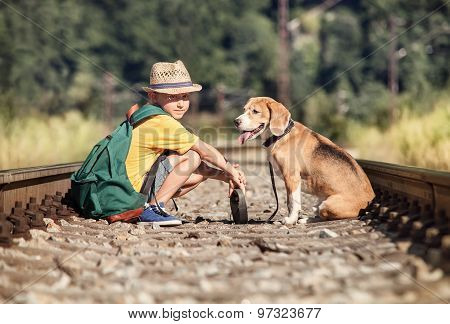 Boy With His Dog Sitting Together On The Railway