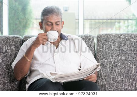Portrait of mature Indian man drinking milk tea while reading on newspaper, sitting on sofa at home. Asian male relax on couch in house with interior.