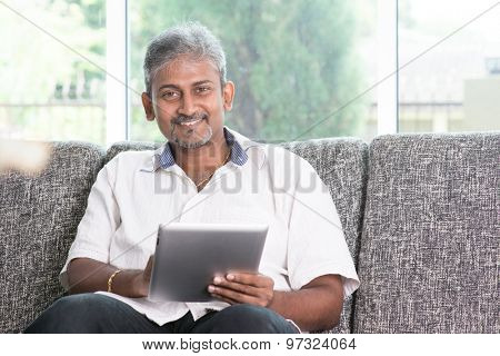 Modern technology. Mature Indian man using touch screen tablet computer at home. Asian people living lifestyle indoors.