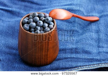 Fresh Wild Blueberries With Wooden Spoon In Wooden Vase On Shabby Indigo Jeans